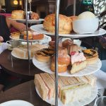 afternoon tea tiers with a selection of savoury and sweet baked goods and english scones.
