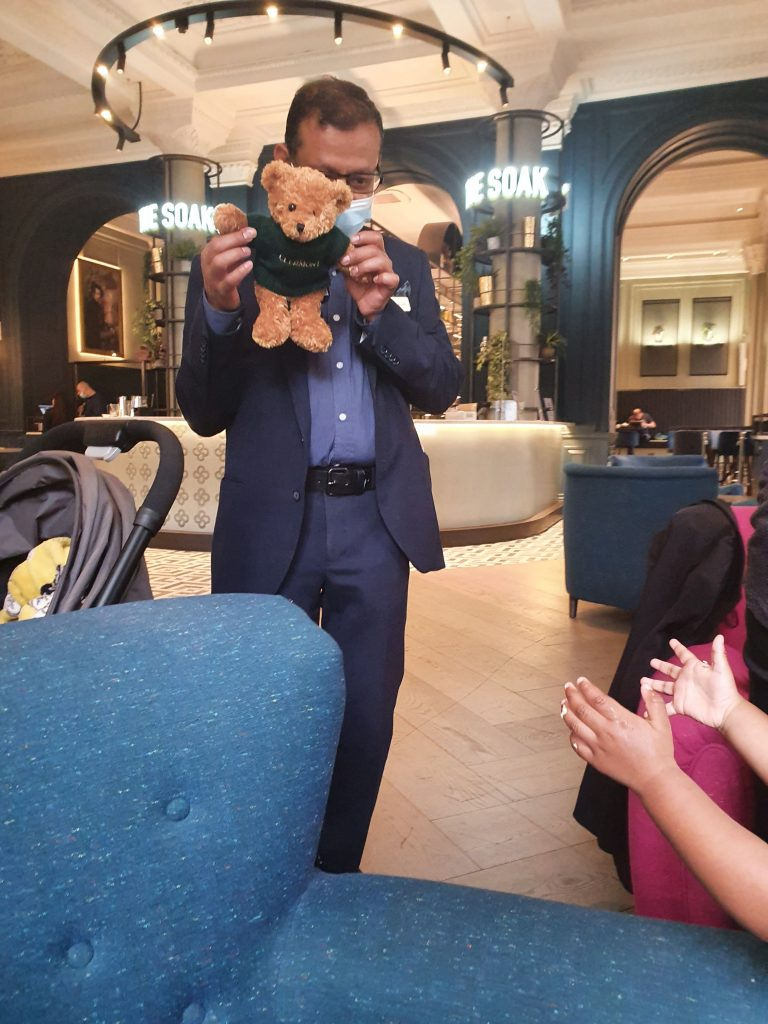hotel staff giving complimentary teddy bear as a birthday gift